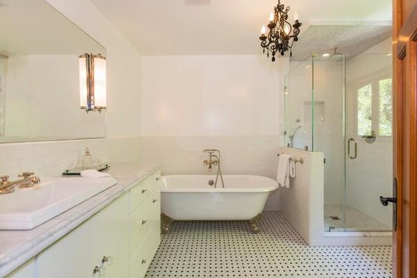 Vẫn là phong cách thiết kế tối giản – minimalism nhưng khác biệt hoàn toàn với phòng tắm vừa rồi, phòng tắm này mang gam màu trắng chủ đạo. Sàn nhà là loại gạch men trắng chấm đen giúp bớt đi sự tẻ nhạt. Bồn tắm với 4 chân kim loại và đèn chùm đã giúp phòng tắm trở nên sang trọng hơn.