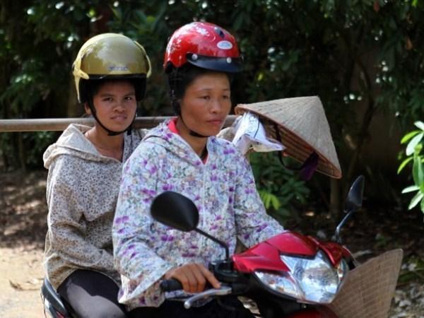 Phụ nữ dân tộc vùng cao vẫn giữ truyền thống búi tóc cao và khi đội mũ bảo hiểm sẽ rất khó khăn. (Ảnh: CTV Xuân Phúc)