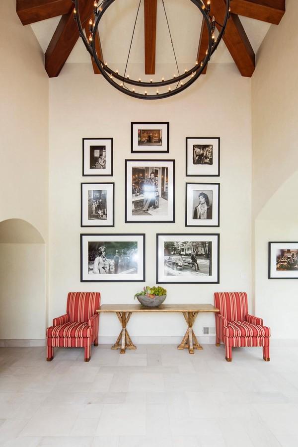 Lối vào ngôi nhà gây ấn tượng với chiếc đèn chùm kim loại lớn treo trên trần nhà gỗ. Ngoài ra lối vào còn được trang trí thêm bằng những khung ảnh của các thành viên trong gia đình, thêm hai chiếc ghế sofa và chiếc bàn gỗ nhỏ giúp gia đình có thể ngồi thư giãn.