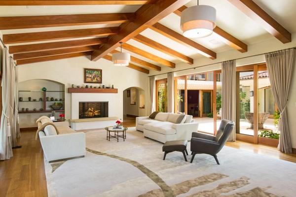 Phòng khách với nội thất giản đơn nhưng không kém phần sang trọng. Gam màu chủ đạo là gam màu trắng, xen lẫn vài màu xám nhẹ nhàng. Bộ ghế sofa màu trắng cỡ lớn được đặt hai bên bếp sưởi, ở giữa kê chiếc bàn nhỏ. Bao quanh phòng khách là những cánh cửa kính trượt sát mặt đất tạo độ thông thoáng và tối đa ánh sáng. Rèm cửa màu ghi nhạt có thể sử dụng để ngăn nắng khi ánh sáng quá chói. Toàn bộ phòng khách được phủ một tấm thảm lông màu trắng tạo nên nét mềm mại.