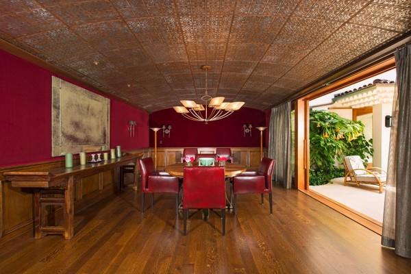 Phòng chờ với gam màu ấm, màu nâu tối của sàn nhà, trần nhà bằng thiếc, toàn bộ tủ, bàn cũng được làm từ gỗ mang tone nâu tối, điểm xuyết thêm vài chiếc ghế cùng mảng tường màu đỏ tía. Gam màu này khiến căn phòng trở nên cổ kính hơn.