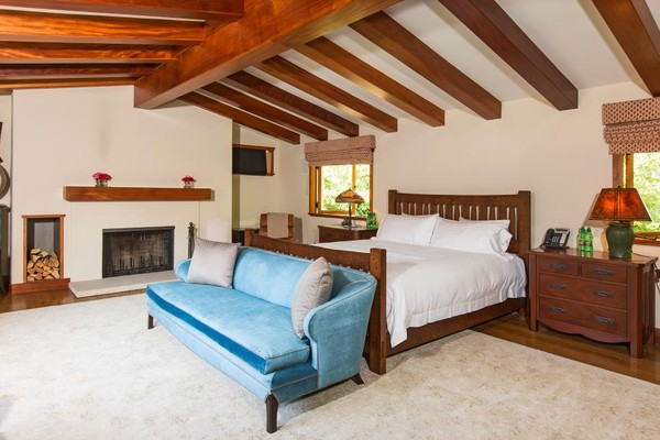 Phòng ngủ mang nét mộc mạc tạo cảm giác yên bình khó tả. Không chút cầu kỳ, giường ngủ chỉ đơn giản là một chiếc giường gỗ như bao chiếc giường thông thường khác. Bộ tủ hai bên giường, hay chiếc ghế, giá để đồ, trần nhà bằng gỗ và bếp sưởi đều tạo cảm giác vô cùng giản đơn và đậm chất rustic. Cuối giường được đặt thêm chiếc ghế sofa màu xanh tạo thành góc trò chuyện nhỏ.