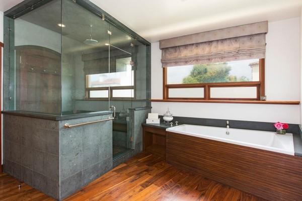 Sàn gỗ màu nâu sẫm kết hợp gạch ốp tường màu xanh đen khiến cho phòng tắm giống như một spa nhỏ. Ngoài bồn tắm bên ngoài, bên trong còn là phòng tắm đứng với bức tường kính trong suốt tạo không gian mở.