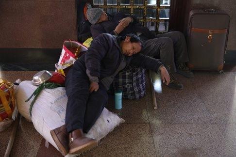 Công nhân ngủ gật chờ chuyến tàu của mình tại nhà ga Foshan