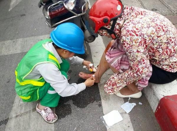 Chị công nhân vệ sinh môi trường giúp người bị nạn sơ cứu vết thương. (Nguồn ảnh: Hòa Phạm)