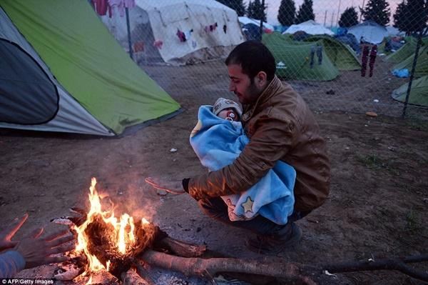 Một người cha phải đưa con đến sát đống lửa để sưởi ấm.