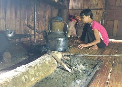 Người phụ nữ đun nấu tại khu nhà phía sau ngôi biệt thự.