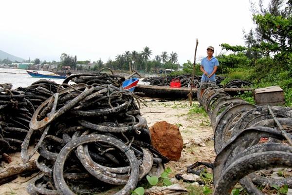 Lốp cao su cũ được người dân kết từng chuỗi rồi thả xuống đầm Lập An.