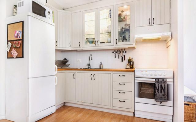 Nhà bếp được thiết kế đơn giản nhưng sang trọng, sự kết hợp màu trắng với điểm nhấn từ tông màu gỗ tự nhiên là cách lựa chọn hài hòa, đẹp mắt. Cách sắp xếp khu vực này cũng khá thông minh. Chủ nhân đã đặt chiếc lò vi sóng lên trên đầu tủ lạnh để tiết kiệm