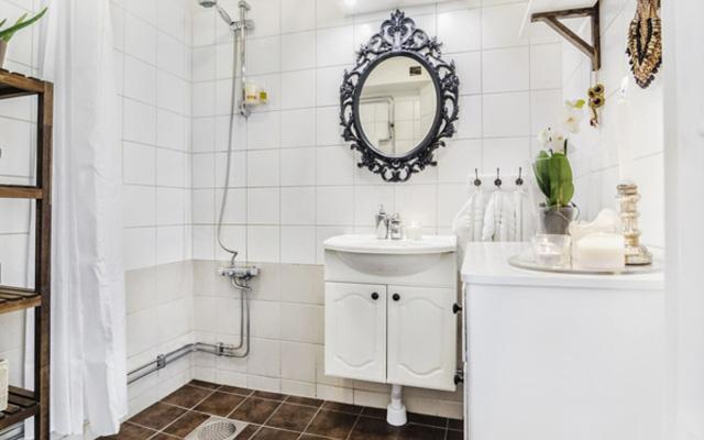 Đằng sau cánh cửa nhỏ màu trắng, bên cạnh tủ đứng lưu trữ là phòng tắm nhỏ nhưng khá cầu kỳ và tiện ích. Bạn sẽ thấy một vòi tắm hoa sen, đèn sưởi, bồn rửa và tủ lưu trữ, kệ gỗ nhiều tầng,… rất đầy đủ và gọn ghẽ.