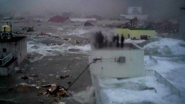Nhân viên ngân hàng 77 mắc kẹt trên nóc nhà khi nước dâng lên (Ảnh: Yoshinori Hara)