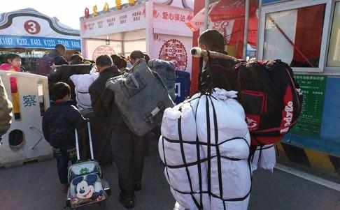 Anh Luo Cheng, một công nhân đang gồng gánh hành lý để về quê ở Hồ Nam
