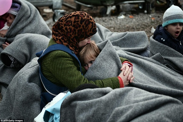 Một người mẹ ủ ấm cho con bằng tấm chăn mỏng.