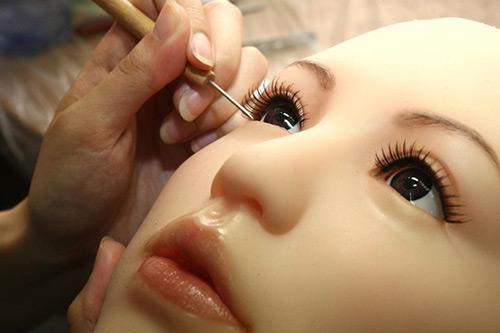 Người thợ đang vẽ mắt cho một con búp bê tình dục