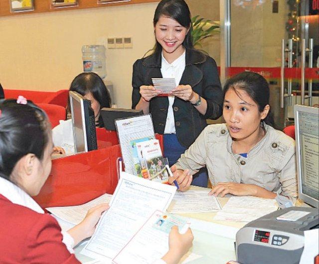 Với CMND 12 số, và sắp tới là thẻ căn cước, sẽ phát sinh những rắc rối liên quan đến thủ tục ngân hàng, thuế... Trong ảnh: khách hàng giao dịch tại Ngân hàng HDBank liên quan đến CMND - Ảnh: Tự Trung