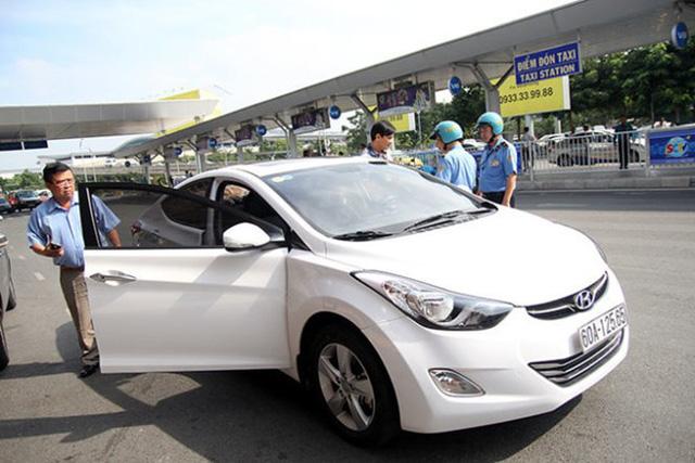 Thanh tra giao thông kiểm tra một chiếc xe chở khách qua dịch vụ Uber tại sân bay Tân Sơn Nhất (TP.HCM).