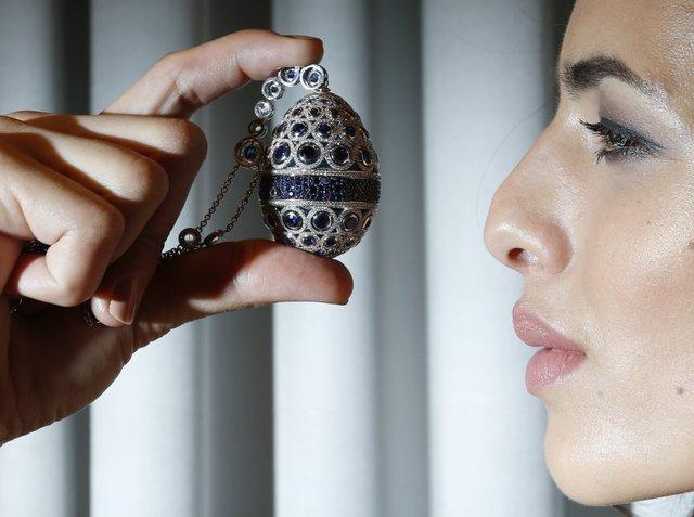 Một người mẫu tạo dáng cùng sợi dây chuyền trứng Faberge tại cửa hàng của thương hiệu nổi tiếng thế giới này