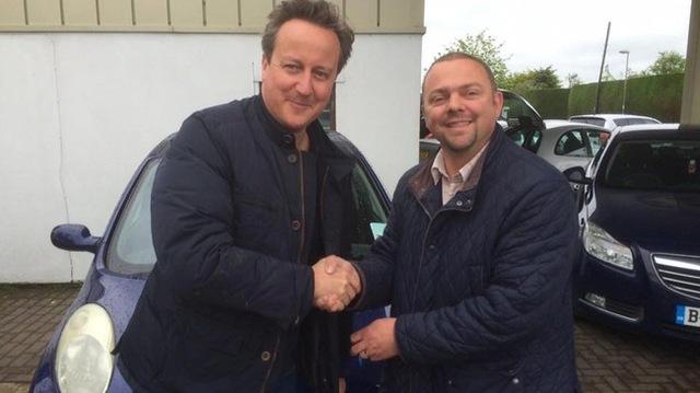 Thủ tướng Anh David Cameron (trái) chụp ảnh lưu niệm với chủ cửa hàng xe cũ.