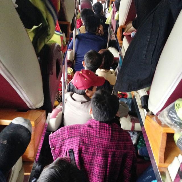 Hành khách trên xe UN-45... từ Lào về, bị nhồi nhét phải ngồi trên lối đi - Ảnh: Doãn Hòa