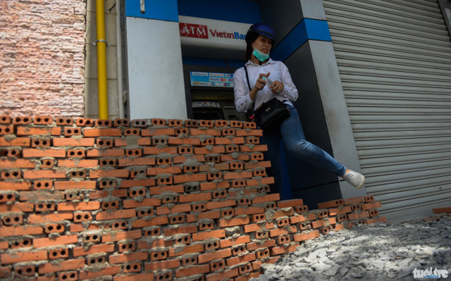 Người dân trèo qua bức tường để vào trụ ATM rút tiền