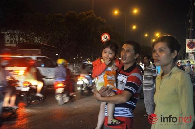 Một em nhỏ chờ xe với bố mẹ