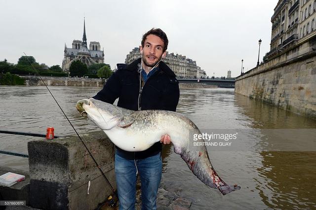 Anh rất phấn khích vì câu được một con cá rất to. Ảnh: Bertrand Guay / AFP