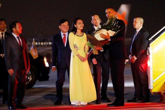 Hình ảnh Trần Mỹ Linh trong tà áo dài tặng hoa chào mừng ông Obama tới Việt Nam (Ảnh: Reuters).