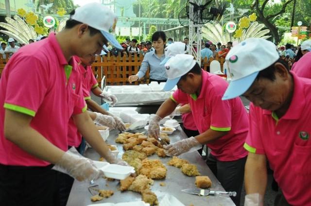 Nhân viên công viên văn hóa Đầm Sen dùng tay chia nhỏ bánh chưng cho người dân - Ảnh: Hồng Lam