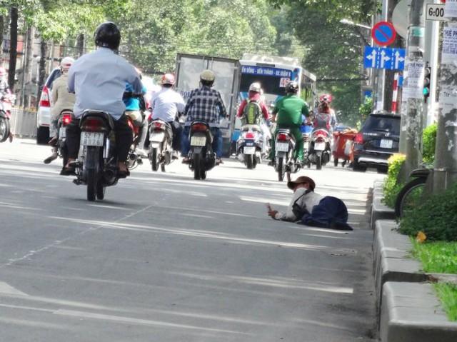 Người nằm bên đường, vừa bán vé số, vừa xin ăn - Ảnh: Mạnh Khang