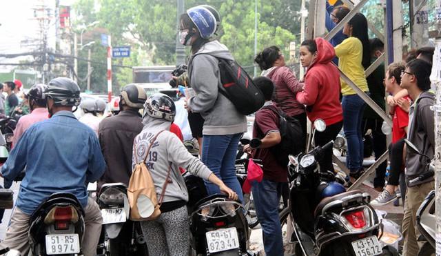 Nhiều nam thanh, nữ tú dừng xe sát con lương, dưới lòng đường để quay phim, chụp hình sự kiện khiến giao thông càng thêm hỗn loạn - Ảnh: Q.Khải