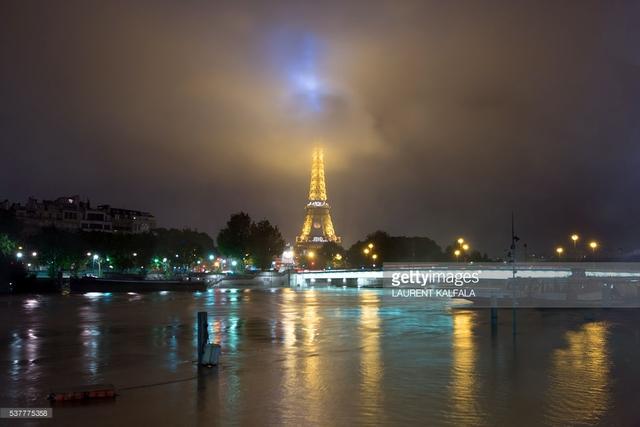 Mặc dù ngập lụt nhưng tháp Eiffel vẫn đứng kiêu hãnh, tự hào là biểu tượng của kinh đô ánh sáng. Ảnh: Laurent Kalfala/ AFP