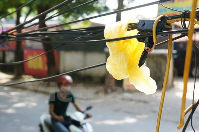 """Hệ thống dây cáp đi nổi được cho là """"rác trời"""" gây mất mĩ quan đô thị ở Thủ đô Hà Nội. (Ảnh: PV/Vietnam+)"""