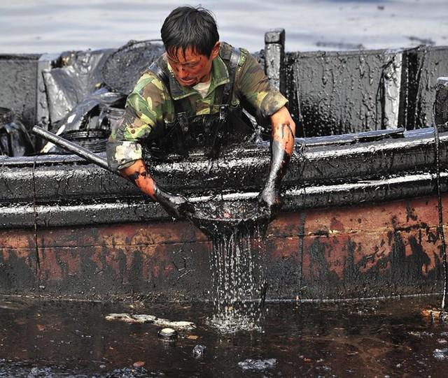 Một công nhân múc dầu ở cảng Đại Liên, Liêu Ninh (Trung Quốc) do vỡ đường ống dẫn dầu, khiến 1.500 tấn dầu thô tràn vào nước. (Nguồn: Techinsider)