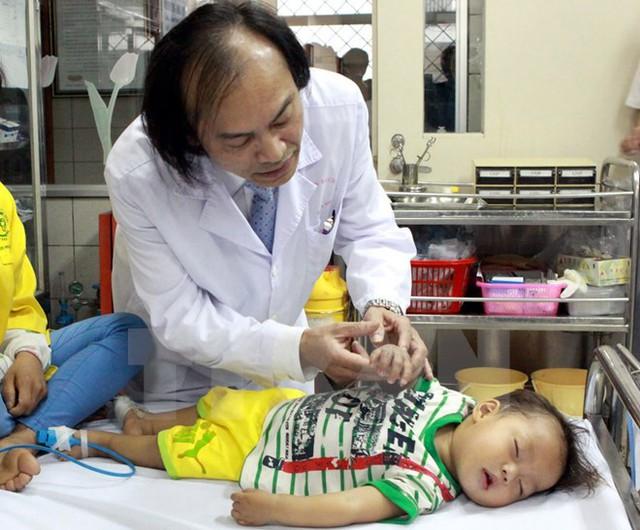 Phó giáo sư Nguyễn Tiến Dũng thăm khám một bệnh nhi. (Ảnh: TTXVN/Vietnam+)