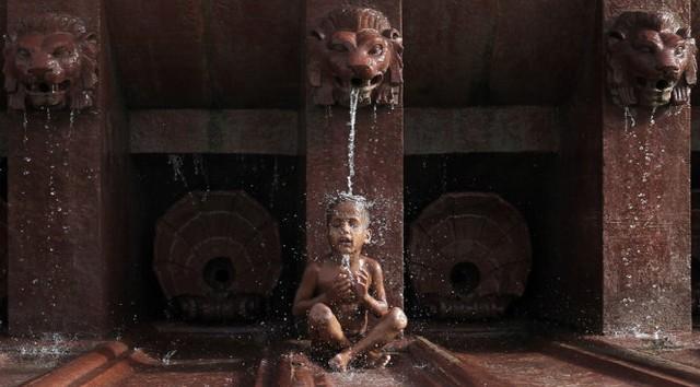 Cậu bé Ấn Độ ngồi dưới vòi nước để giải nhiệt ở New Delhi - Ảnh: Reuters