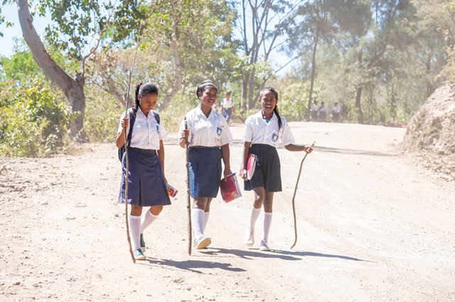Nữ sinh Đông Timor đi bộ đến trường giữa trưa trên con đường đầy bụi mịt mù
