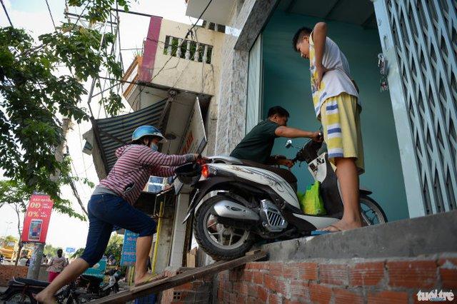 Vợ chồng chị Phạm Thị Vê Lô (P.An Lạc, Q.Bình Tân) phải bắc cầu đẩy xe vào nhà