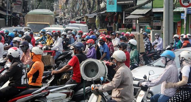 Hàng trăm phương tiện dồn ứ trên đường Nguyễn Phúc Nguyên nối ra vòng xoay Dân Chủ, phía xa xa là một xe cấp cứu bị kẹt trong đám đông kẹt xe - Ảnh: Q.Khải