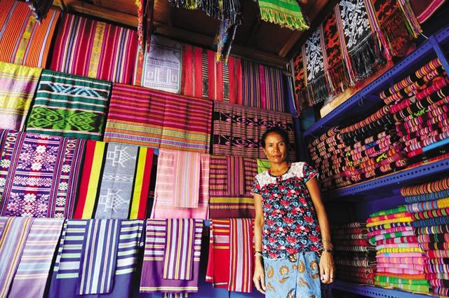 Một phụ nữ bán khăn Tais truyền thống dệt bằng tay ở chợ thủ đô