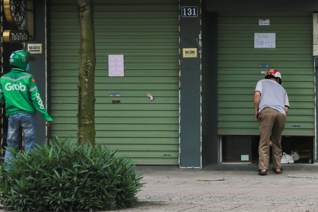 Ảnh: Cửa hàng mở hé cửa, mua bán thò thụt trong những ngày cách ly xã hội - Ảnh 4.