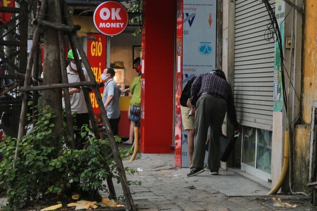 Ảnh: Cửa hàng mở hé cửa, mua bán thò thụt trong những ngày cách ly xã hội - Ảnh 7.