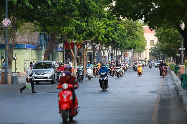 [Ảnh] Đường phố nhộn nhịp trở lại, các phương tiện chen chân chờ đèn đỏ ngày đầu tiên hết cách ly toàn xã hội ở TP.HCM - Ảnh 13.