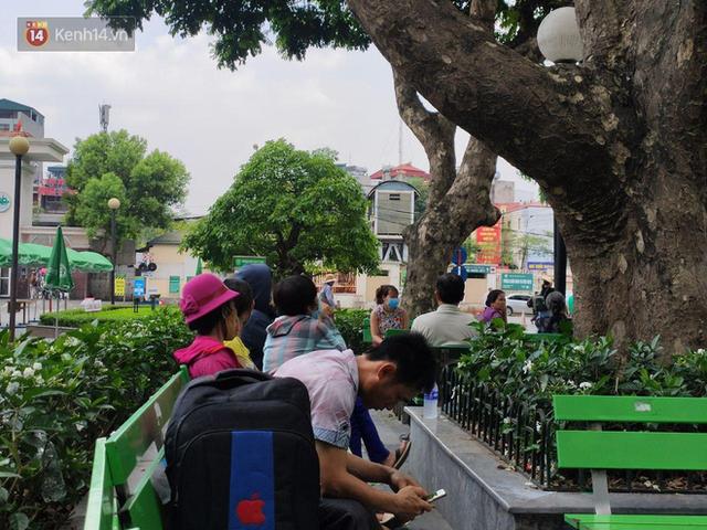 Ảnh: Nắng nóng gần 40 độ C ở Hà Nội, người nhà bệnh nhân vạ vật gần hành lang, dưới bóng cây trong bệnh viện - Ảnh 13.