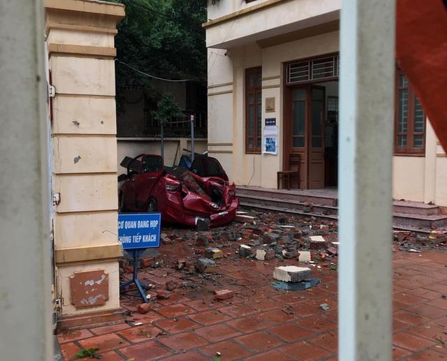 Mưa lớn kèm lốc xoáy khiến bức tường đổ sập, đè bẹp chiếc ô tô đang đậu dưới sân - Ảnh 1.