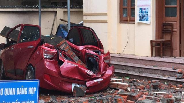 Mưa lớn kèm lốc xoáy khiến bức tường đổ sập, đè bẹp chiếc ô tô đang đậu dưới sân - Ảnh 2.