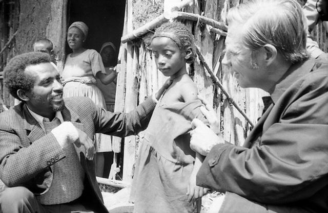 Bác sĩ Henderson kiểm tra vết sẹo tiêm chủng trên tay một cô bé Ethiopia