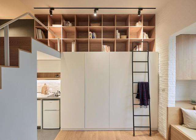 Tủ được thiết kế sát tường và có khu vực lưu trữ đồ trang trí, sách vở phía trên. Chiếc thang với bánh xe dễ di chuyển có thể được sử dụng để lấy vật dụng, bài trí khu vực phía bên trên tủ quần áo.