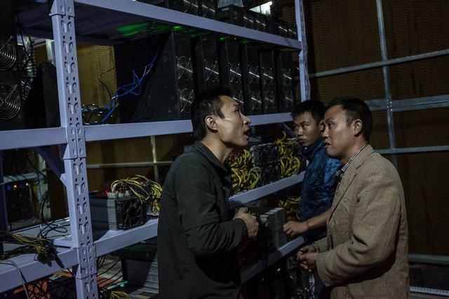 Thợ đào Liu (bên phải) gặp đối tác tại nơi làm việc của mình ở Tứ Xuyên. Liu chuyển từ Hà Nam về Tứ Xuyên vào năm 2015 với mong muốn tìm được một nguồn điện năng rẻ hơn. Hiện nay, anh đang quản lý hơn 7.000 máy đào cho đối tác tại khắp Trung Quốc.