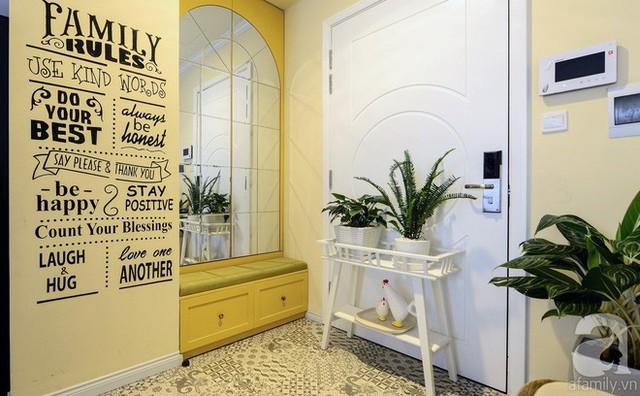Khu tiền sảnh của căn hộ đơn giản mà bắt mắt với nền gạch hoa, mảng trang trí bằng chữ ấn tượng và cây xanh.