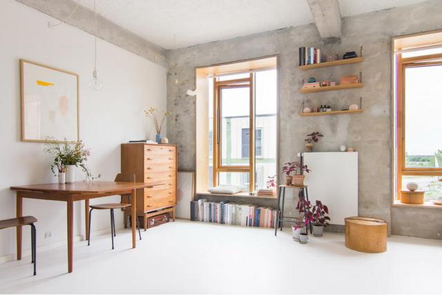 Căn hộ studio rộng 25m² không được chia nhỏ ra các phòng mà được phân vùng bằng chính nội thất cần thiết. Không gian rộng thoáng nhờ có cánh cửa sổ cao và rộng được lắp đặt chất liệu kính với khung gỗ thân thiện.